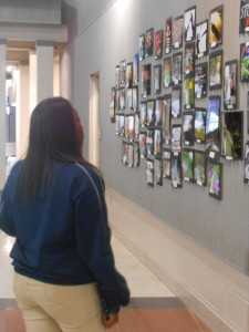 Yasmine Jones, an 8th grade photography student, looks over images that she has displayed in the Snaptastic Wildcat Exposure photography exhibit.